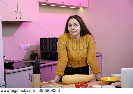 Young Woman Cooking In A Kitchen. Housewife Preparing Vegetables For Cooking. Peel Yellow Zucchini.