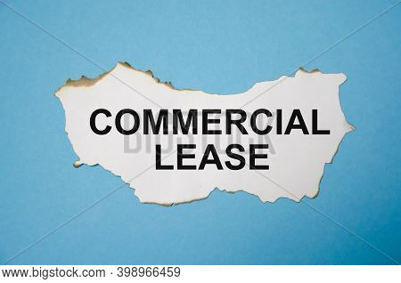 The Text Commercial Lease Is Written On A White Sheet Of Paper That Lies On A Blue Background
