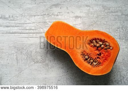 Half Of An Oblong Red Pumpkin With Seeds Lies On The Kitchen Table.