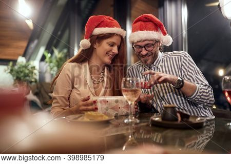 young caucasian couple exchanging presents with santa hats. christmastime,