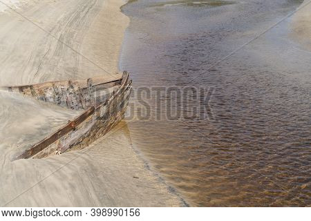 Lines And Patterns Curving Along Edge Of Mill Creek Interupted By Bow Of Old Wooden Boat  Stuck In S