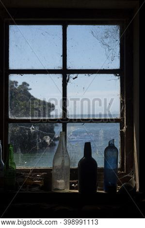 Old Bottles Standing On Window Sill Of Multi-paned Window With View Through To Coastal Scene On Stew