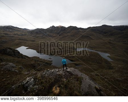 Person In Blue Jacket Infront Of Andes Hills Tundra Grassland Lakes Landscape In El Cajas National P