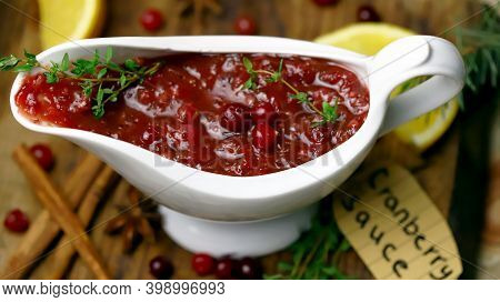Cranberry Sauce In A White Gravy Boat. Cranberries, Cinnamon And Spices. Branches Of A Christmas Tre