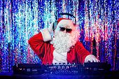 DJ Santa Claus mixing up some Christmas cheer. Disco lights in the background. poster