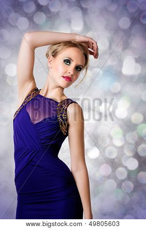 young beautiful woman with up style blond hair wearing tight blue evening dress with gold luxury design on her fit slim body over lights studio background