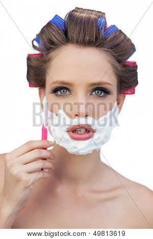 Young model in hair curlers posing with shaving foam and razor on white background