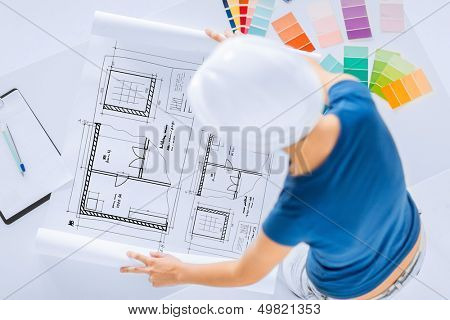 architecture, interior design and renovation concept -  woman in helmet working with color samples and blueprint poster