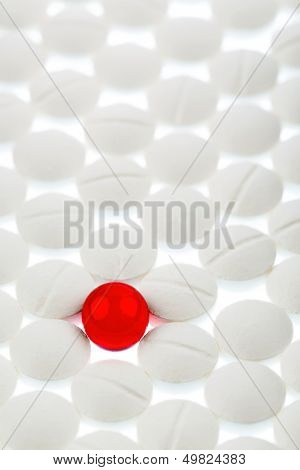 white tablets in contrast with a red tablet, symbolic photo for bullying and individuality