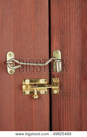 Metal hook and deadbolt in wooden door close-up