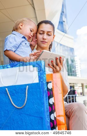Mother and her son looking at the tablet, shopping bags beside them