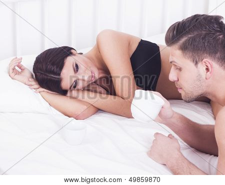 Young sexy passionate couple with coffee in bed