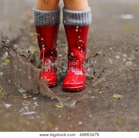 Child Wearing Red Rain Boots Jumping Into A Puddle