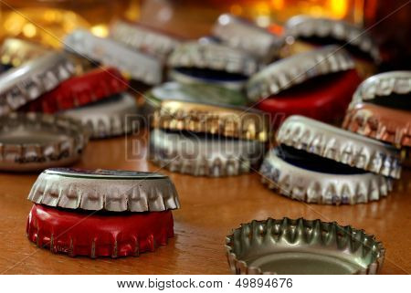Assortment of bottle caps on wood bar with glasses of beer reflecting light in the background.  Macro with shallow dof.