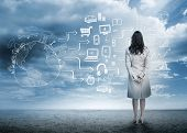 Businesswoman looking out at brainstorm drawings in cloudy landscape poster