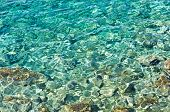 Rocky sea floor visible thru crystal clear turqoise water of Aegean sea in Greece poster