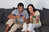 Young Couple on Sofa Playing Video Games poster