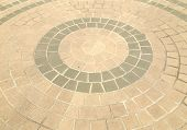 pavement of cobble stones in a circle pattern poster