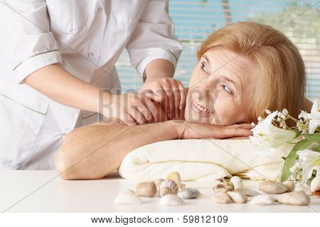 Beautiful Caucasian elderly woman at a reception in the spa salon poster