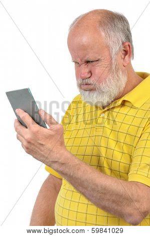 senior bald man wih puffed up cheeks looks into mirror