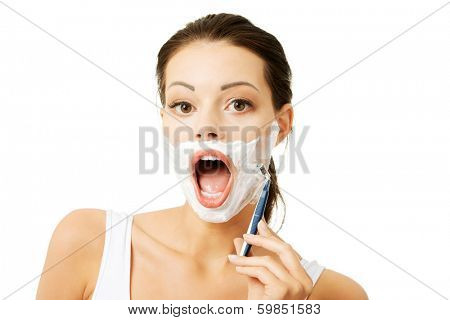 Beautiful young woman shaving her face with a razor