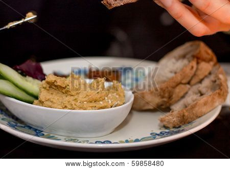 Plate Of Hummus Cucumber And Bread With Hand And Knife
