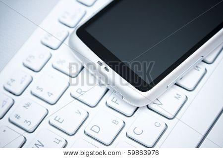 Smart Phone Over White Keyboard