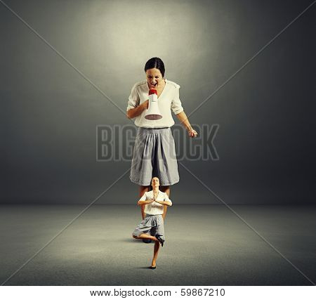 concept photo of self reproach. angry big woman screaming at small yoga woman