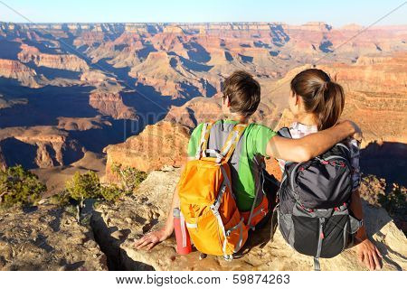 Hiking hikers in Grand Canyon enjoying view of nature landscape. Young couple relaxing during hike wearing backpacks on South Kaibab Trail, south rim of Grand Canyon, Arizona, USA.