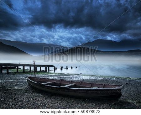 Old Boat On Lake Of Shore With Misty Lake And Mountains Landscape With Stormy Sky Overhead