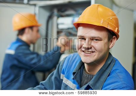 Happy young adult electrician builder engineer in front of his co-worker screwing equipment in fuseboard poster