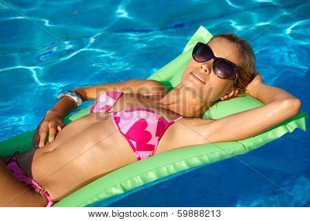 Pretty young girl laying on airbed in swimming pool, relaxing, sunbathing.