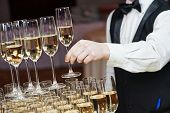 Waiter hand with glass of champagne over pyramid during catering at party poster