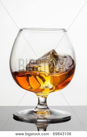 Splash of whiskey with ice in glass isolated on white background. Raw image, no postproduction