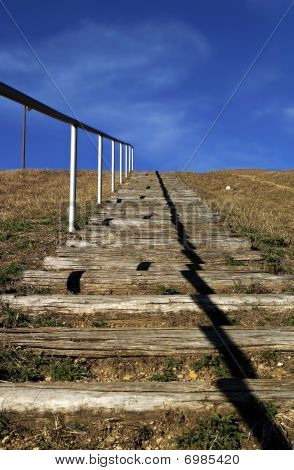 Picture of wooden stairs gouing up to the sky, concept of reaching high goal poster