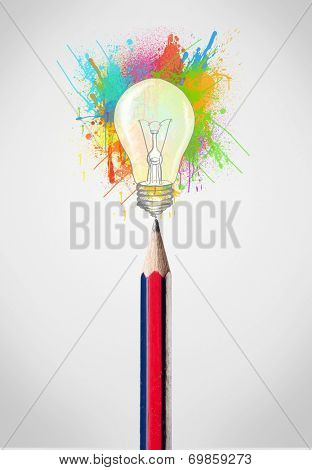 Colored pencil close-up with colored paint splashes and lightbulb concept