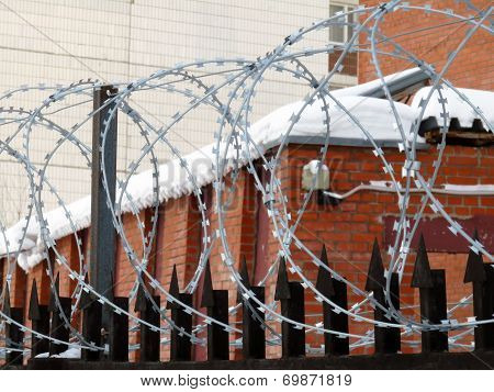 Fence Topped With Barbed Wire On The Background Of An Apartment House