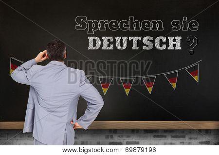 Thinking businessman against blackboard on wall, Do you speak German?