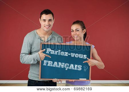 Smiling young couple pointing at sign they are holding against blackboard with copy space on wooden board, Do you speak French?
