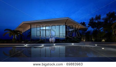 Illuminated swimming pool in front of an upmarket tropical villa with a modern angular design, glass facade and patio decorated with potted plants on a tranquil twilight evening