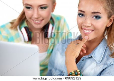 Twom young women sitting together with a laptop at home