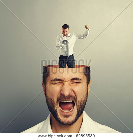 stressed businessman with open head. young angry man standing into the head, looking at the man and screaming with megaphone. photo over grey background