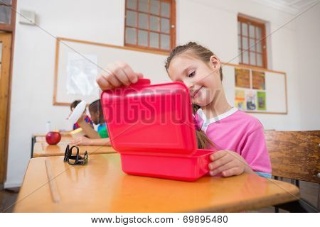 Cute pupil opening lunchbox at desk in classroom at the elementary school