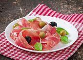 Ham, olives, basil on old wooden background poster