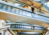 People in motion in escalators at the modern shopping mall poster