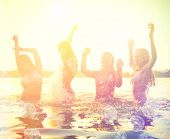 Group of happy teen girls playing in water at the beach on sunset. Beauty and joyful teenager friends having fun, dancing and spraying over summer sunset. Beach party. Sun flare. poster