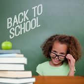 Cute pupil tilting glasses against back to school message poster
