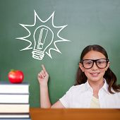 Cute pupil pointing against red apple on pile of books poster