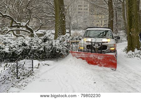Truck with snowplow on road after snowstorm