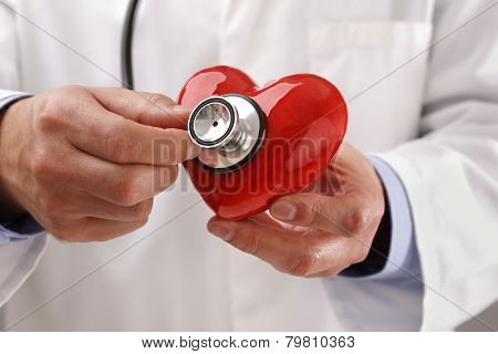 Doctor or cardiologist holding heart listening to heartbeat concept for healthcare and diagnosis medical cardiac pulse test